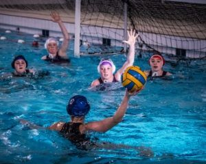 players int he water playing waterpolo