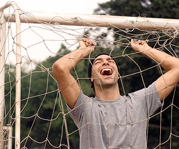 Man laughing in football net