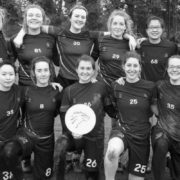 Women's Frisbee team posing for team photo with frisbee