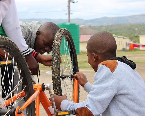 south african fixing bikes and smiling