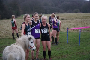 Cross country runners posing for a photo with a white shetland pony