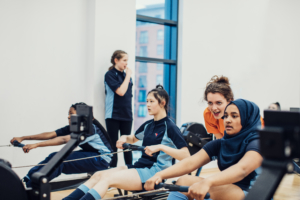 students on rowing machines with volunteers encouraging them