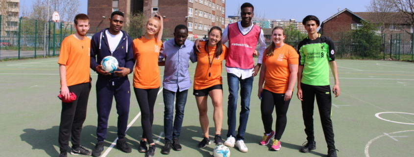 volunteers with refugees as part of the football and language refugee programme - posing for a photo